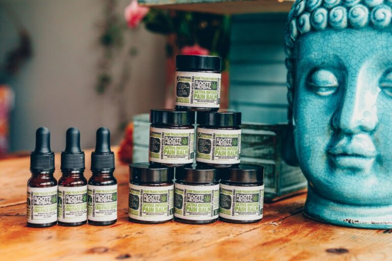 CBD oils on a wooden table with a Large Buddha head