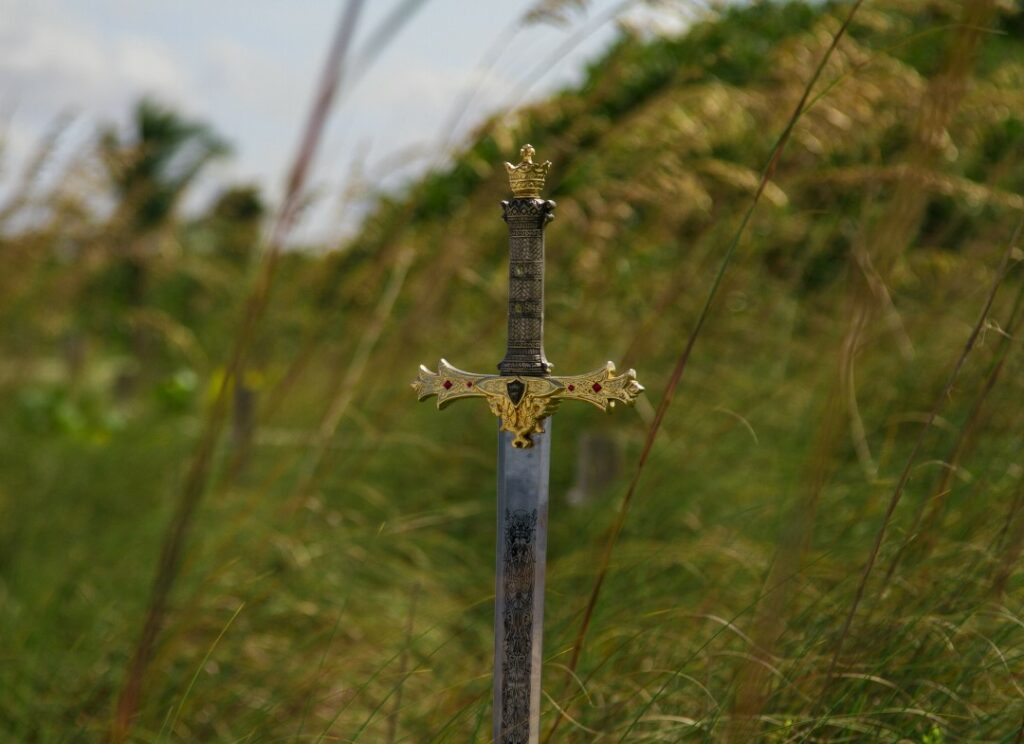 Medieval sword in the ground green hill